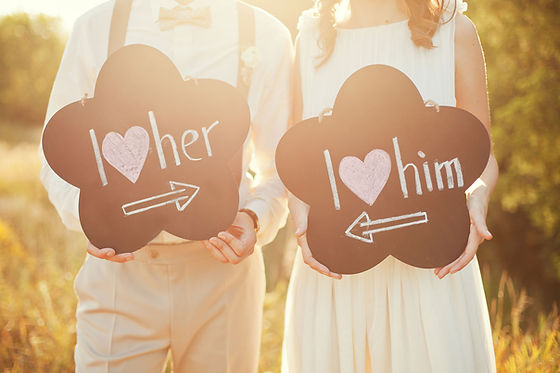 "Couple holdingsigns saying, ""I love her,"" and ""I love him."""