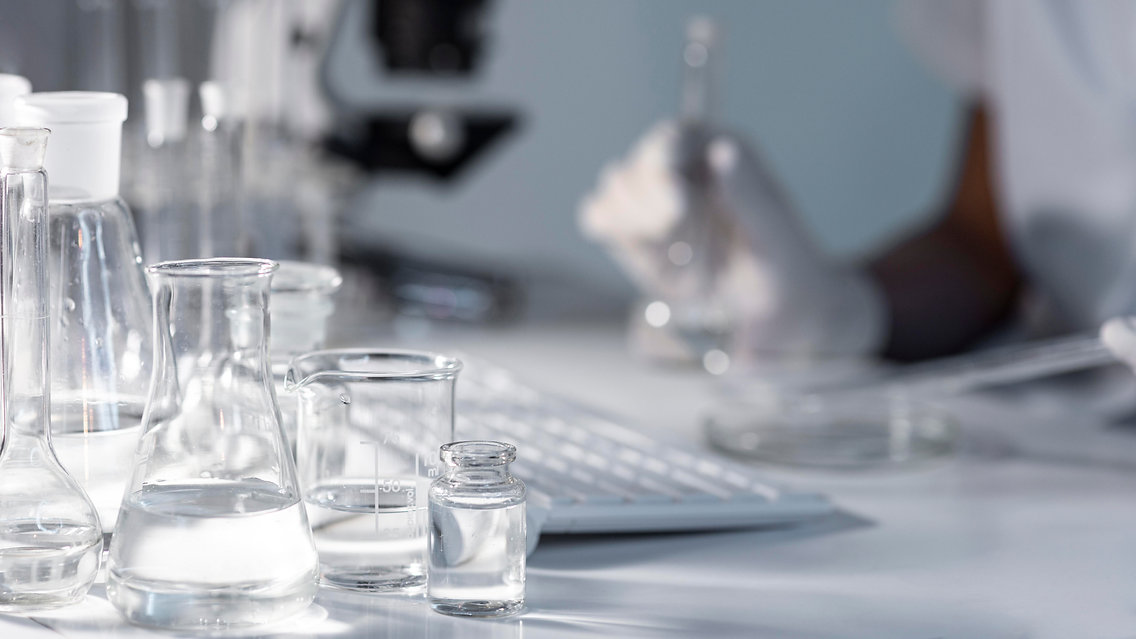 close-up-blurry-researcher-holding-glass