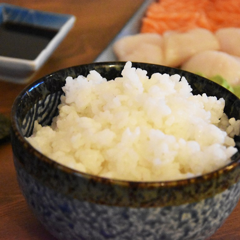 A bowl of Sushi rice with a platter of sashimi