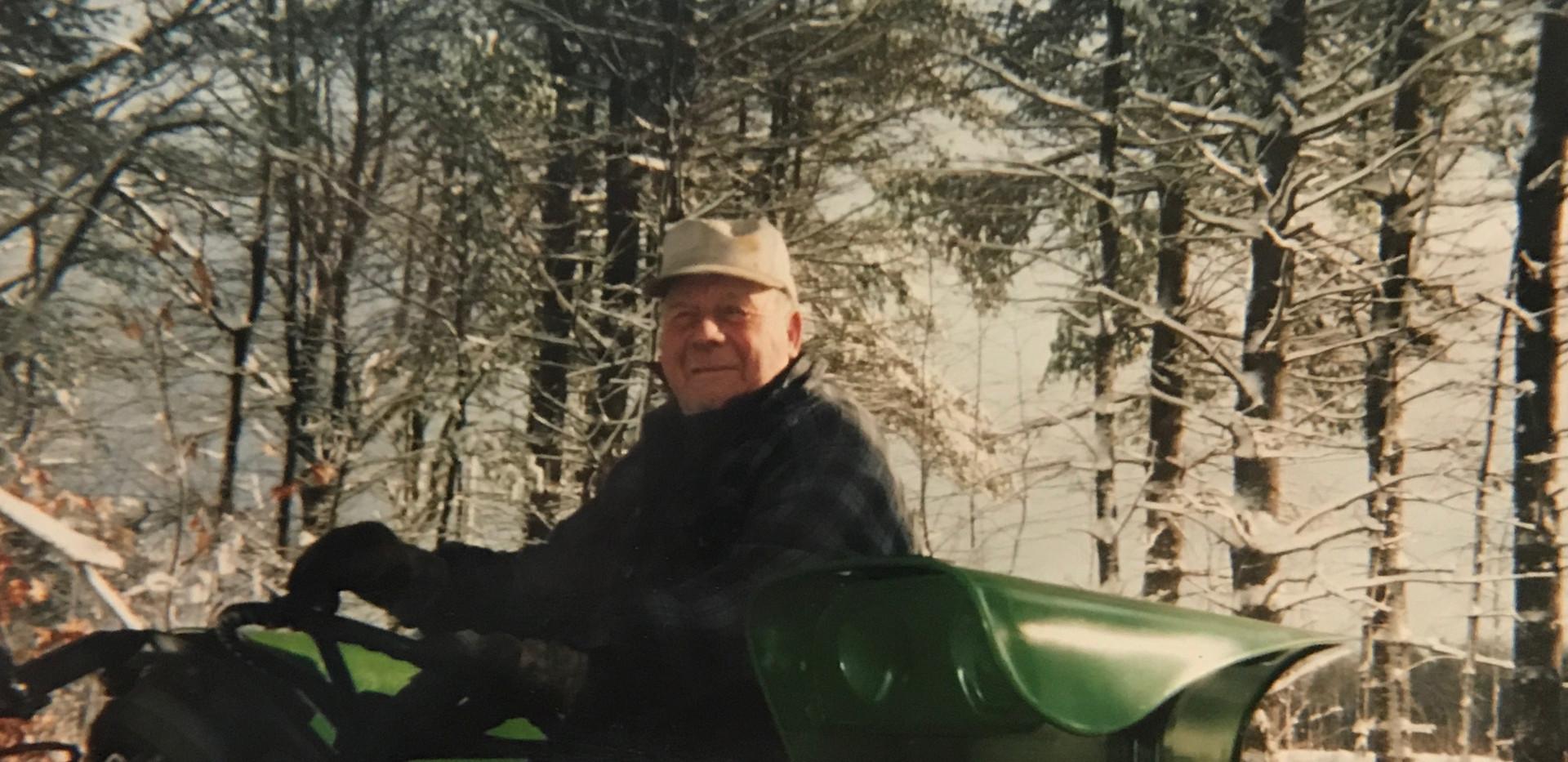 Farmer Othro (Tom) Sawyer atop his John Deere tractor