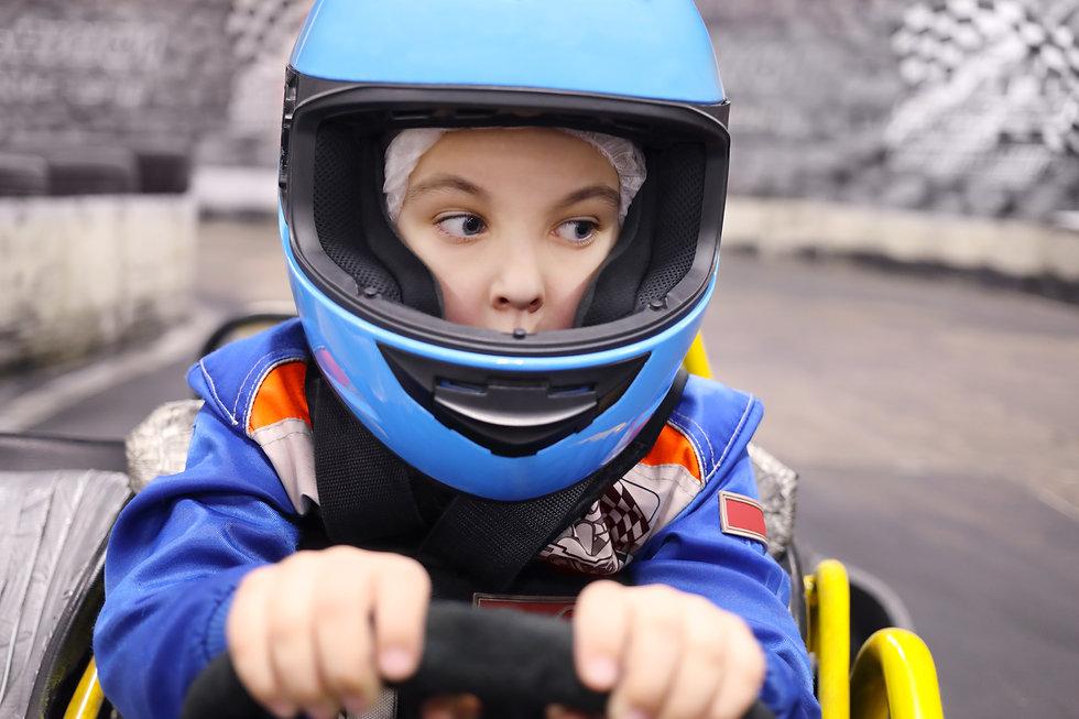 Little funny boy in helmet drives in go-