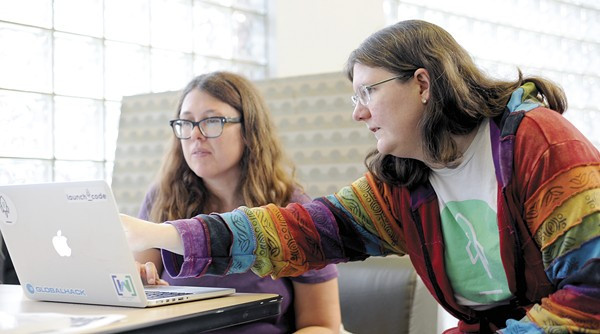 Two women work on a laptop together
