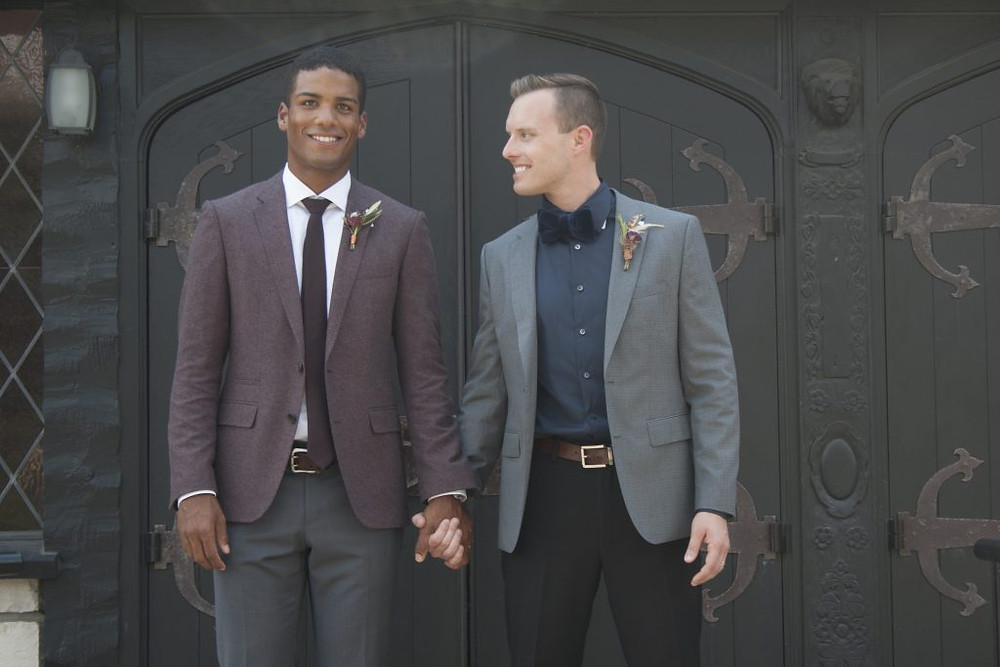 Two grooms hold hands in front of a door in a photo for Alive Magazine