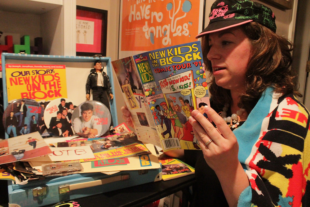 A woman wears a New Kids on the Block hat and towel while reading a NKOTB comic and looking at memorabilia