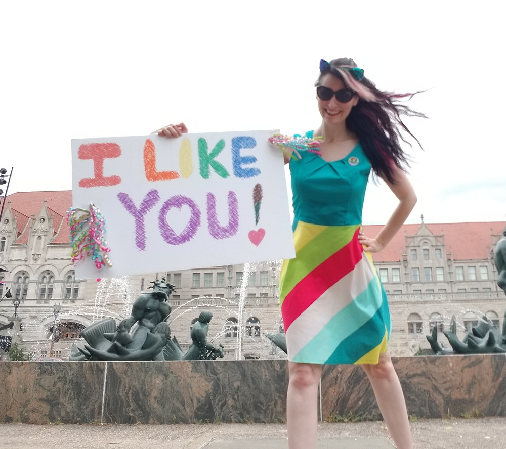 """Allison Babka in a rainbow dress holding a sign that says """"I like you"""""""