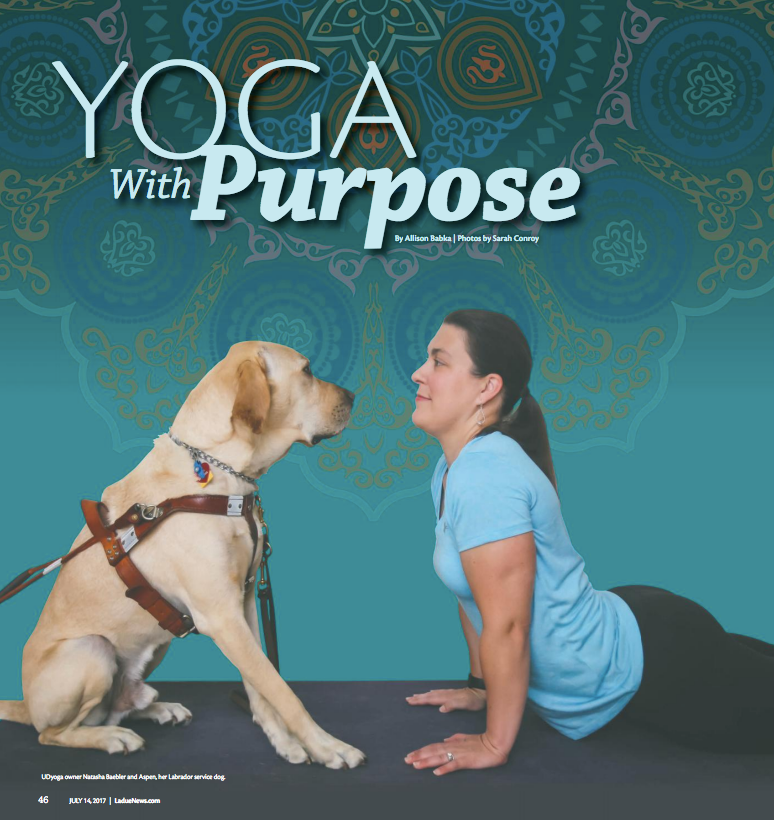 A woman does yoga on the floor while facing her service dog