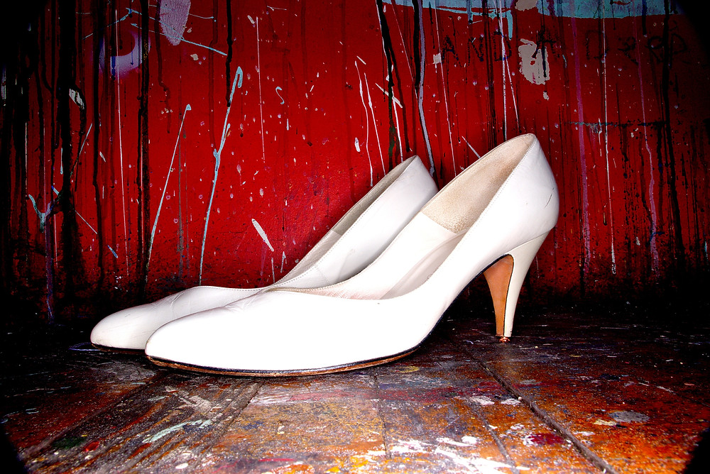 White kitten heel shoes on a red floor