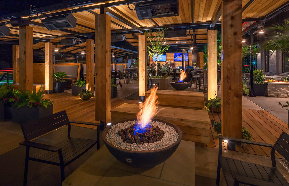A large exterior patio and cover made of wood with a fire pit and chairs