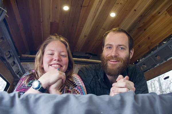A man and woman smile at the camera while laying on a bed in their van home