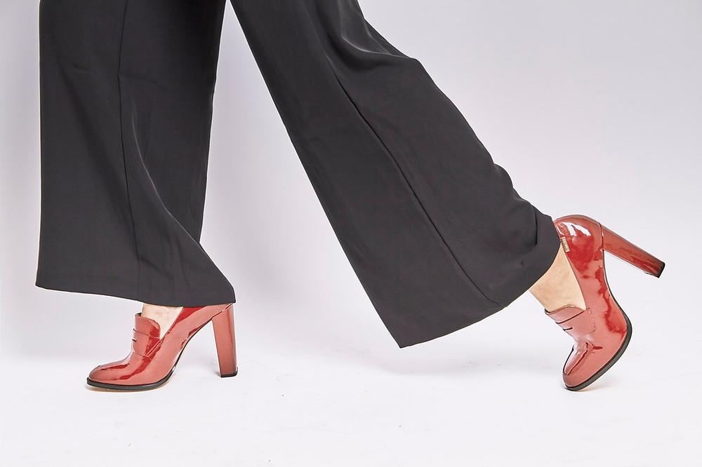 Closeup of a woman's legs walking, wearing black pants and red heels