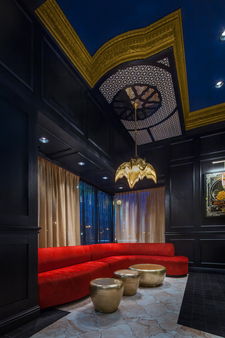 Restaurant and bar interior with a long red banquette sofa and blue and gold ceilings