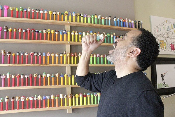 A man stands in front of hundreds of Pez dispensers and pretends to flip a candy into his mouth