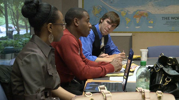 Three students sit at a table with laptops and notes