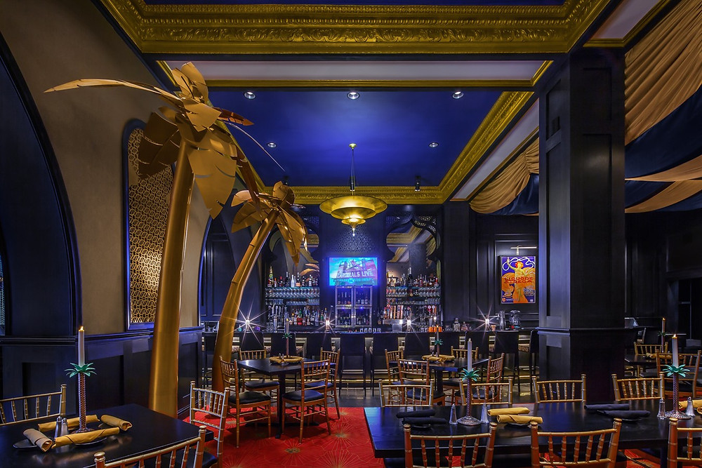 Restaurant and bar interior with tables, chairs, a high blue and gold ceiling and giant gold palm trees