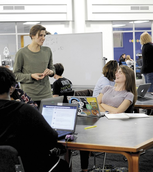 A woman stands near a table of other women who are working on laptops in a class