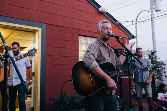 Billy Bragg holds a guitar and speaks into a microphone