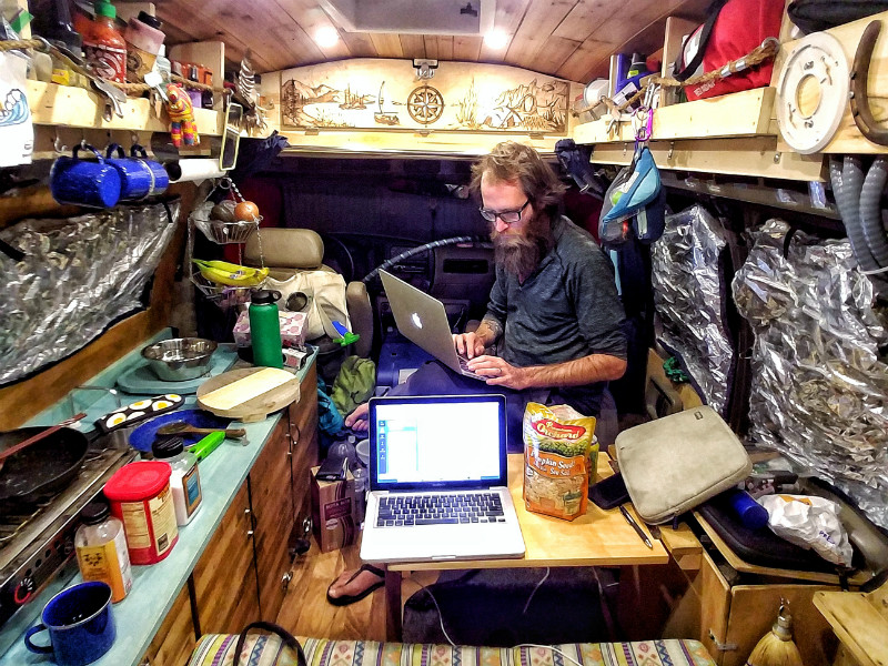 A man types on a laptop computer at a small table in his van home
