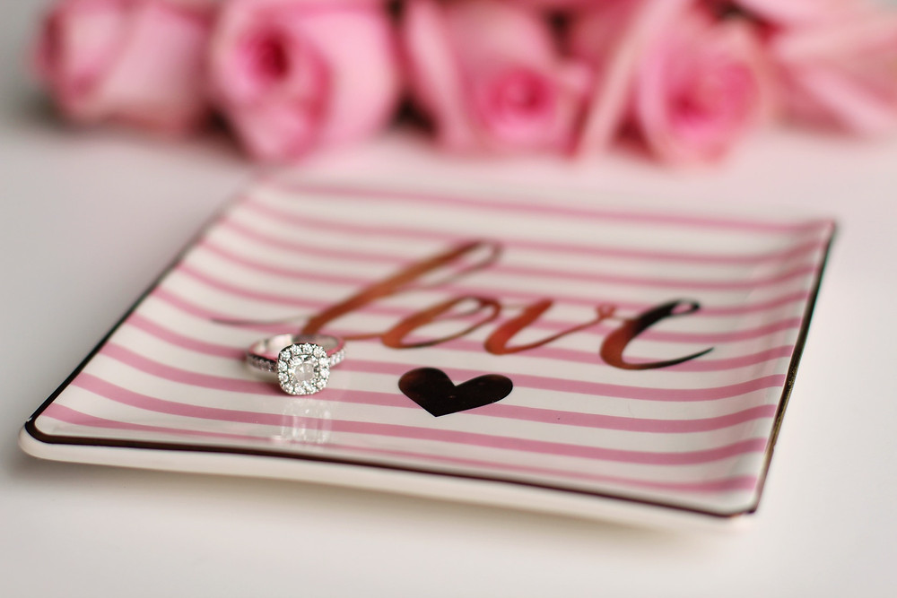 """A large engagement ring resting on a square pink and white striped plate that says """"love"""""""