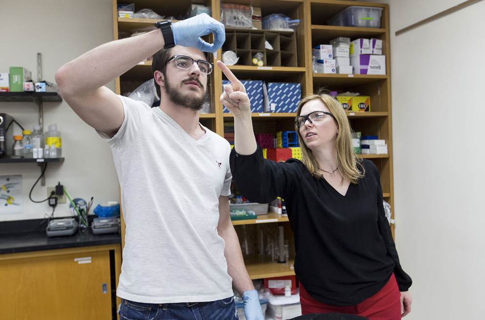 A female professor points at something a male student is holding in a lab