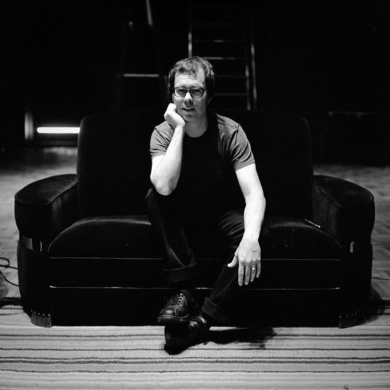 Ben Folds wears glasses and sits on a black velvet loveseat