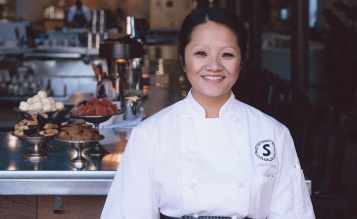 Chef Diane Yang wears her pastry chef jacket while standing in front of a table full of her desserts