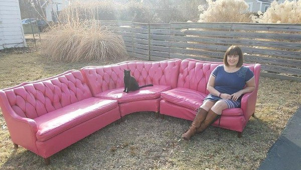 A woman in a blue dress and a black cat sit on a large pink sofa