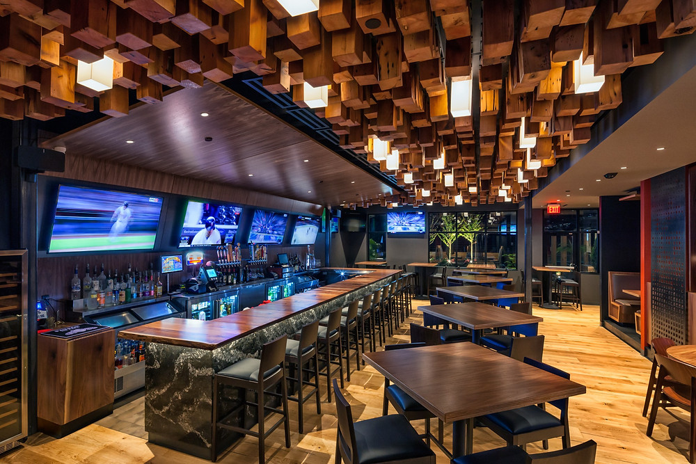 Restaurant and bar interior outfitted with wood and televisions