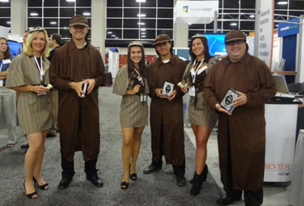 Three women and three men hold cards at a trade show while dressed like Sherlock Holmes