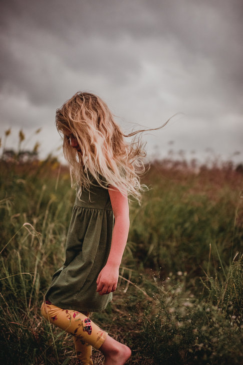 Girl in Grass on A Gloomy Day