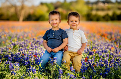 Young Boys Sitting In A Flower Field