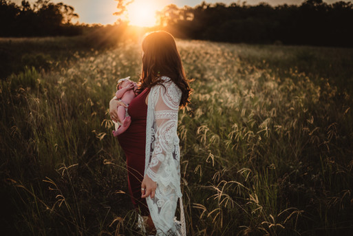 Woman Holding Newborn Baby in a Field