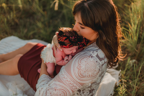 Newborn Baby with Woman Sitting in Grass