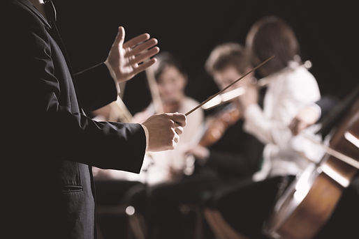 Photo of a conductor leading an orchestra