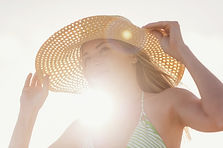 Woman holding a hat on her head to shield away the sun