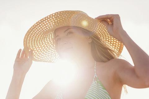 Genç kadın-in-sun-şapka-on-the beach, -J