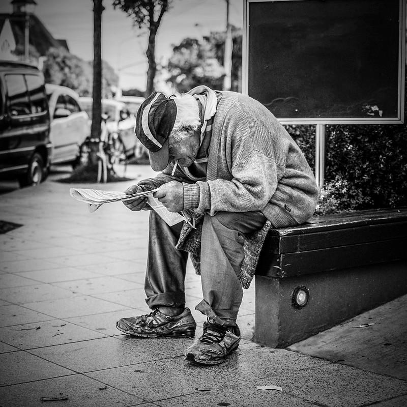 een oude man die een krant leest op straat
