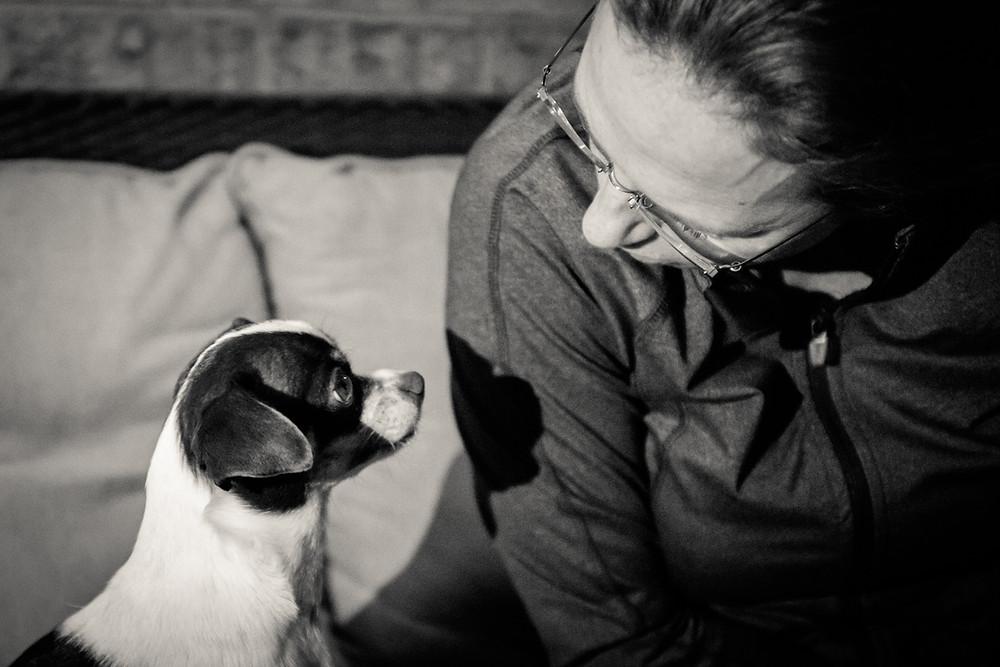 Een meisje praat tegen haar hondje.
