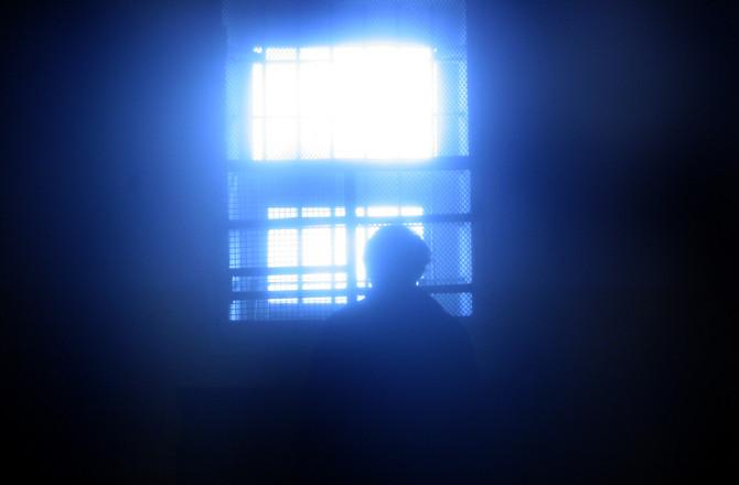Pessoa presa numa cela.