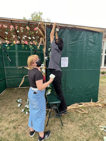 Isabel and Mikey hang flowers on the Sukkah