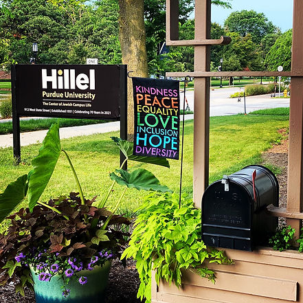Hillel Purdue University sign, inclusive sign, mailbox and plants