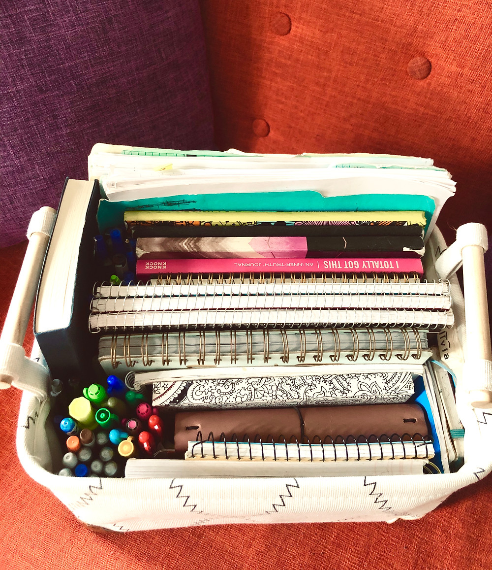 a photos of a notebook collection in a basket sitting on top of an orange couch