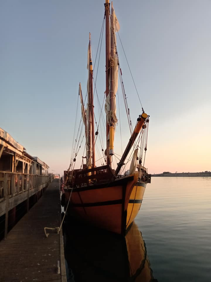 Le bateau l'Ange Gardien est amarré à la terrasse d'un restaurant au Grau d'Agde, sur fond de coucher de soleil.