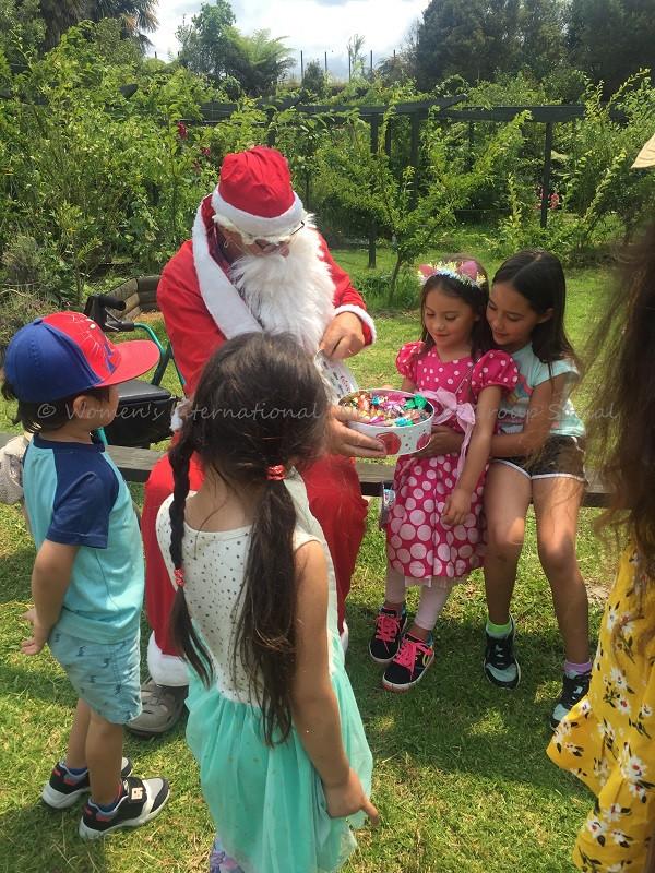 Santa distributing candies to children