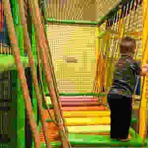 toddler crossing an indoor playground bridge