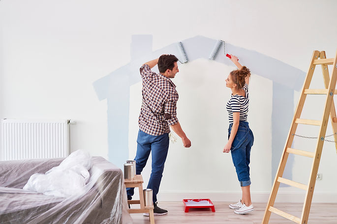 Young couple painting the interior wall
