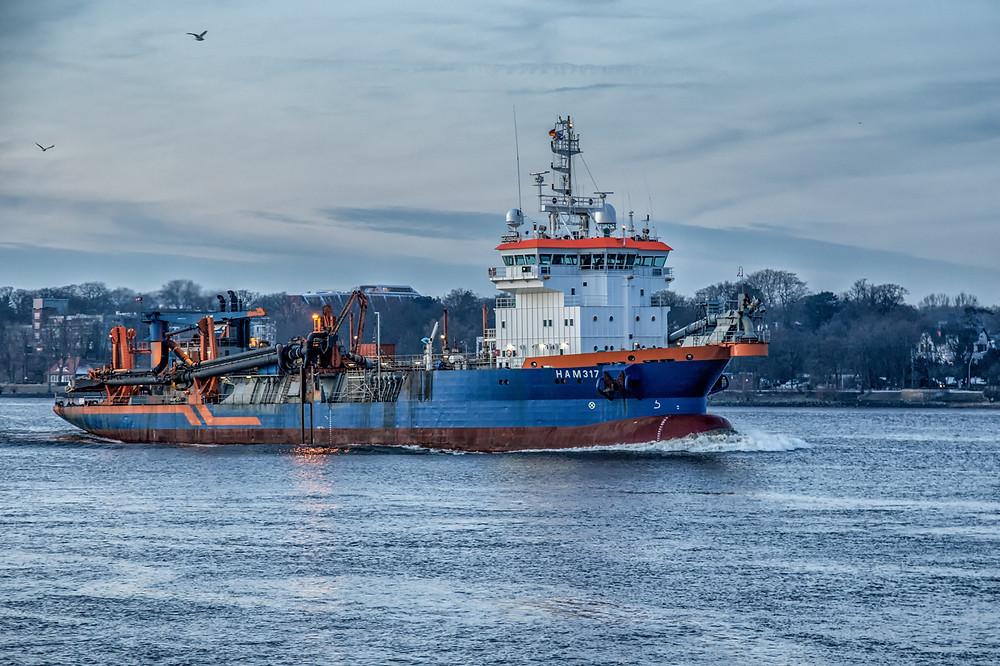 Der Saugbagger HAM316 im Hamburger Hafen, fotografiert zur blauen Stunde.
