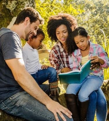 familia-feliz-leyendo-juntos-debajo-de-u