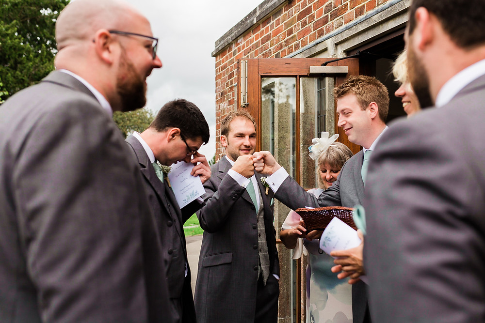 groomsman fist bumping the groom