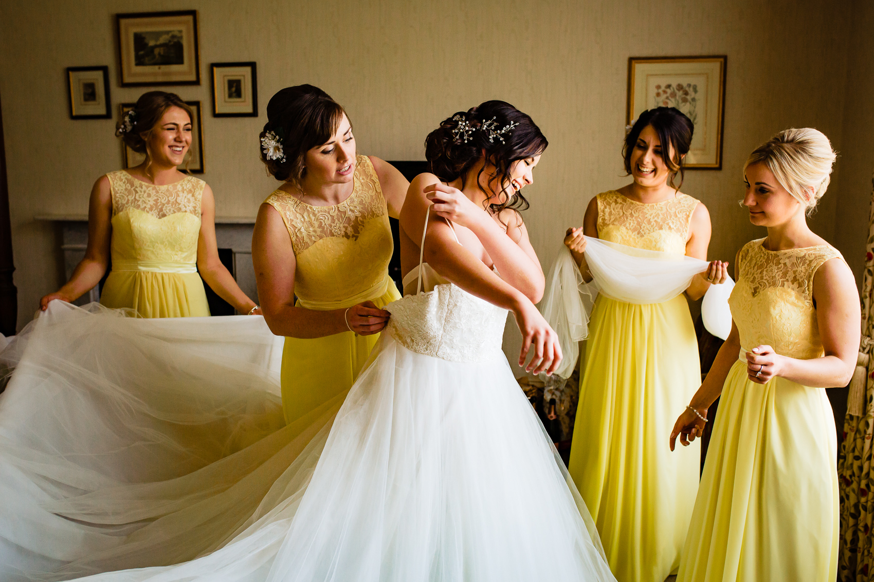 putting on a wedding dress with bridesmaids