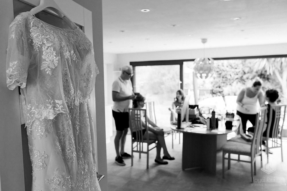 wedding dress hung on door